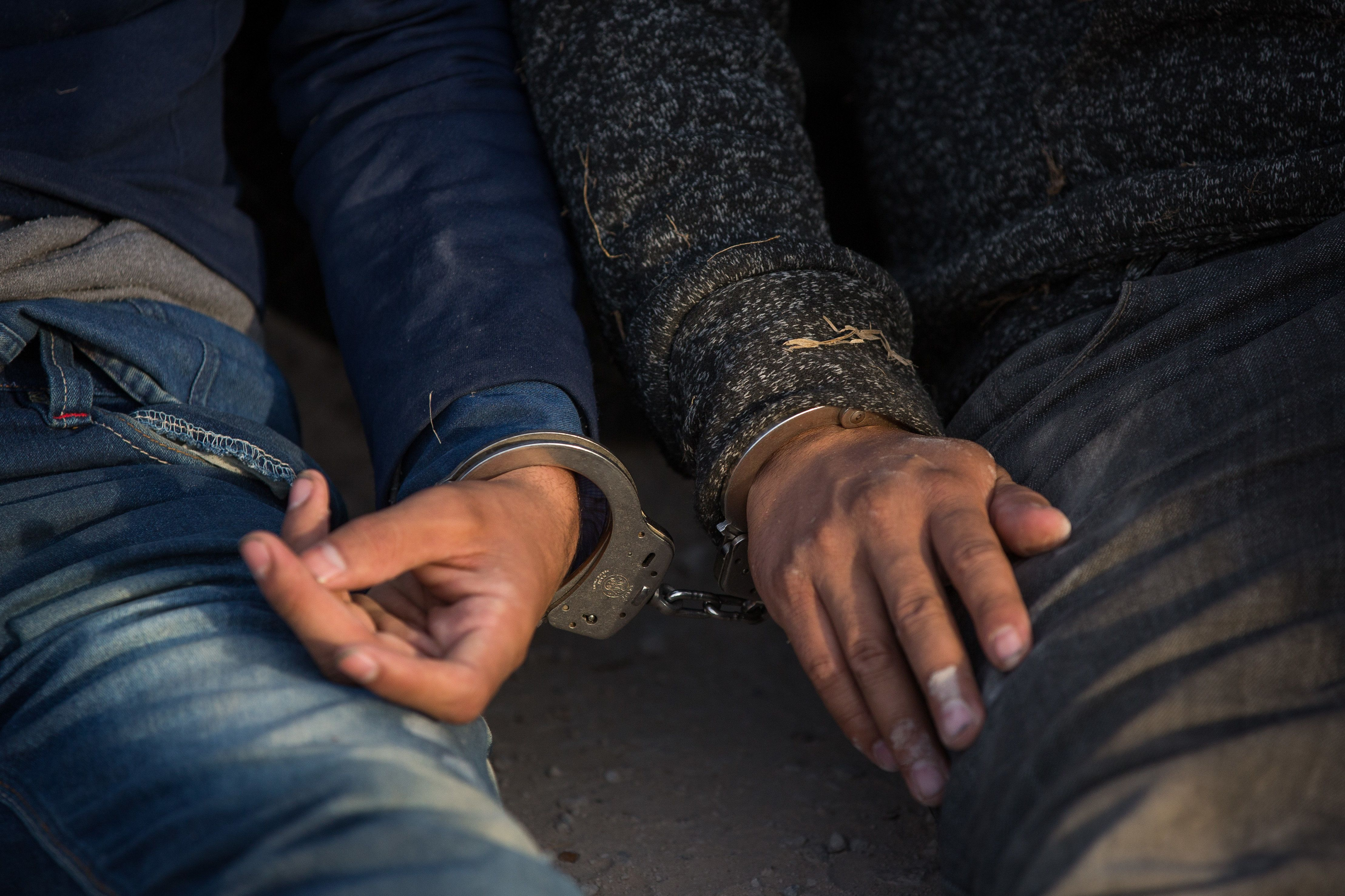 Two immigrants apprehended by Border Patrol wait to be transported to a central processing center after crossing the border f