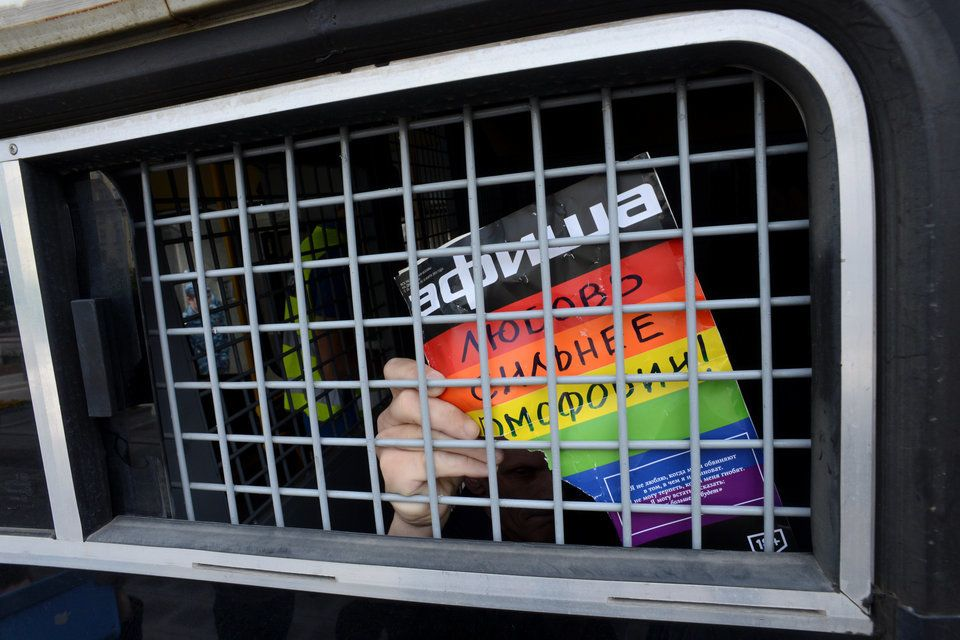 An unknown gay-rights activist in a police vehicle in Moscow. His sign says: 'Love is stronger than homophobia'.