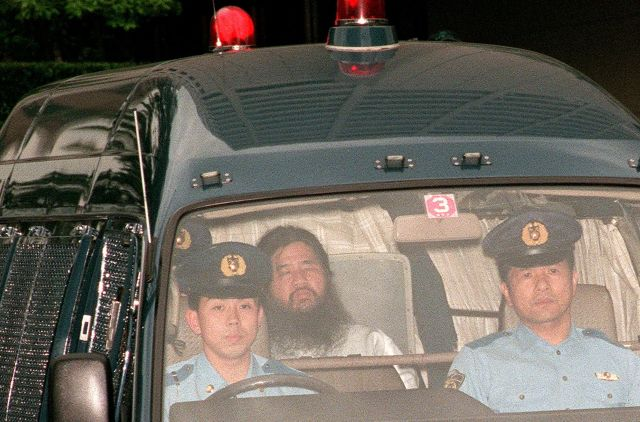 In this picture taken on July 19, 1995, Shoko Asahara (C), head of the doomsday cult Aum Shinrikyo, is transferred from Tokyo