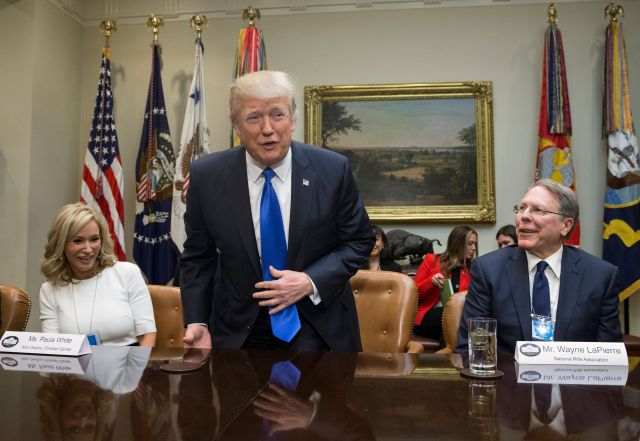 President Donald Trump takes a seat between White and National Rifle Association leader Wayne LaPierre at a White H