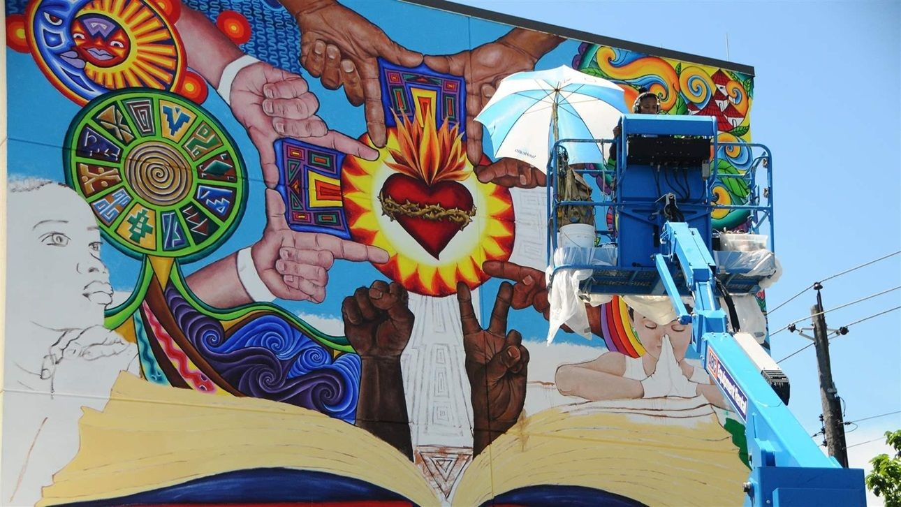 Artist Michelle Santos at work on a mural near the Sacred Heart of Jesus Church in southeast Baltimore.