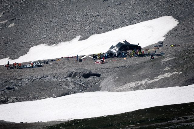 Accident investigators and rescue personnel gather around the wreckage of a Junkers JU52 aircraft at Flims on August 5, 2018,