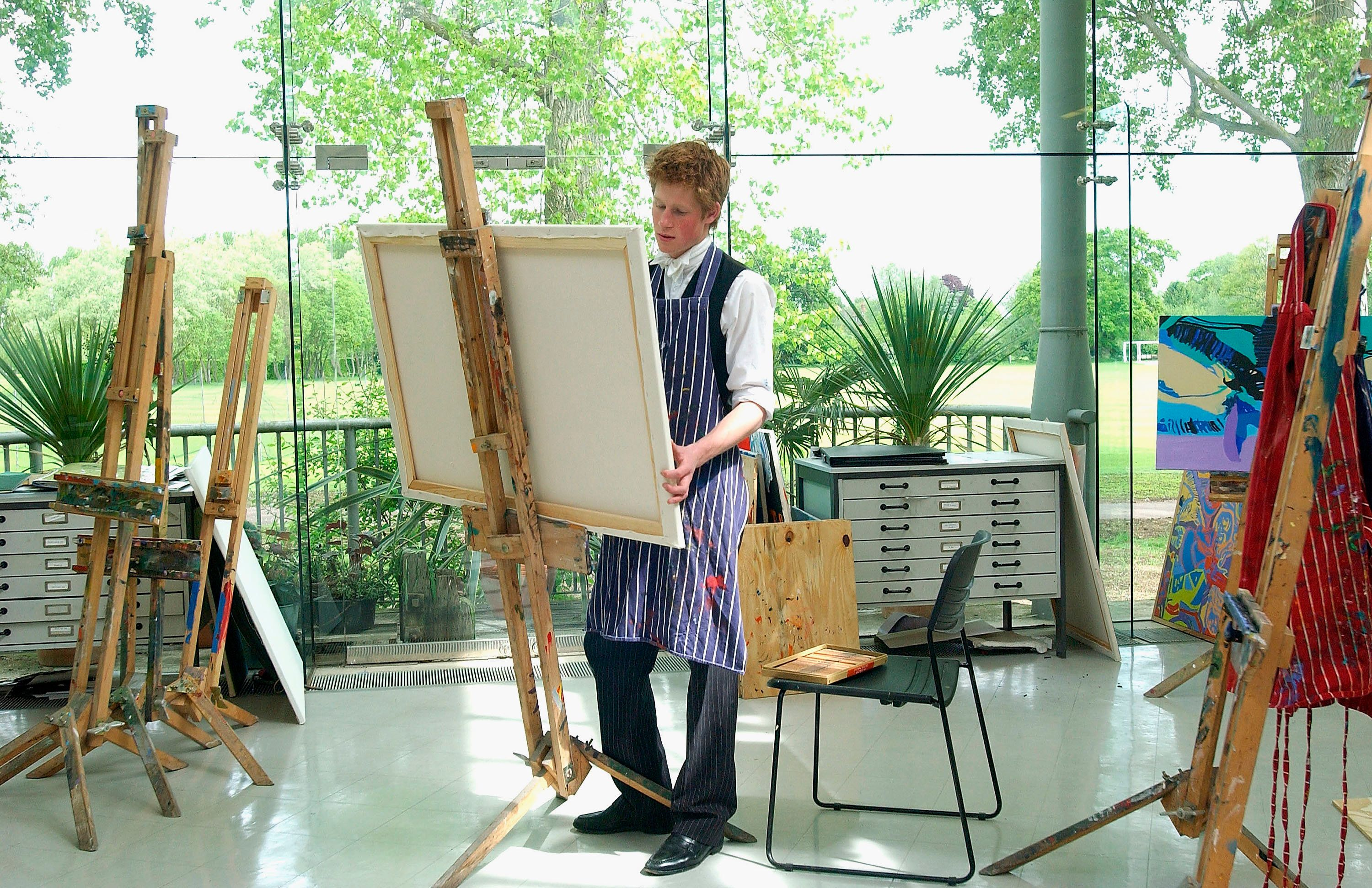 Prince Harry poses painting in the Drawing Room at Eton College on May 12, 2003.