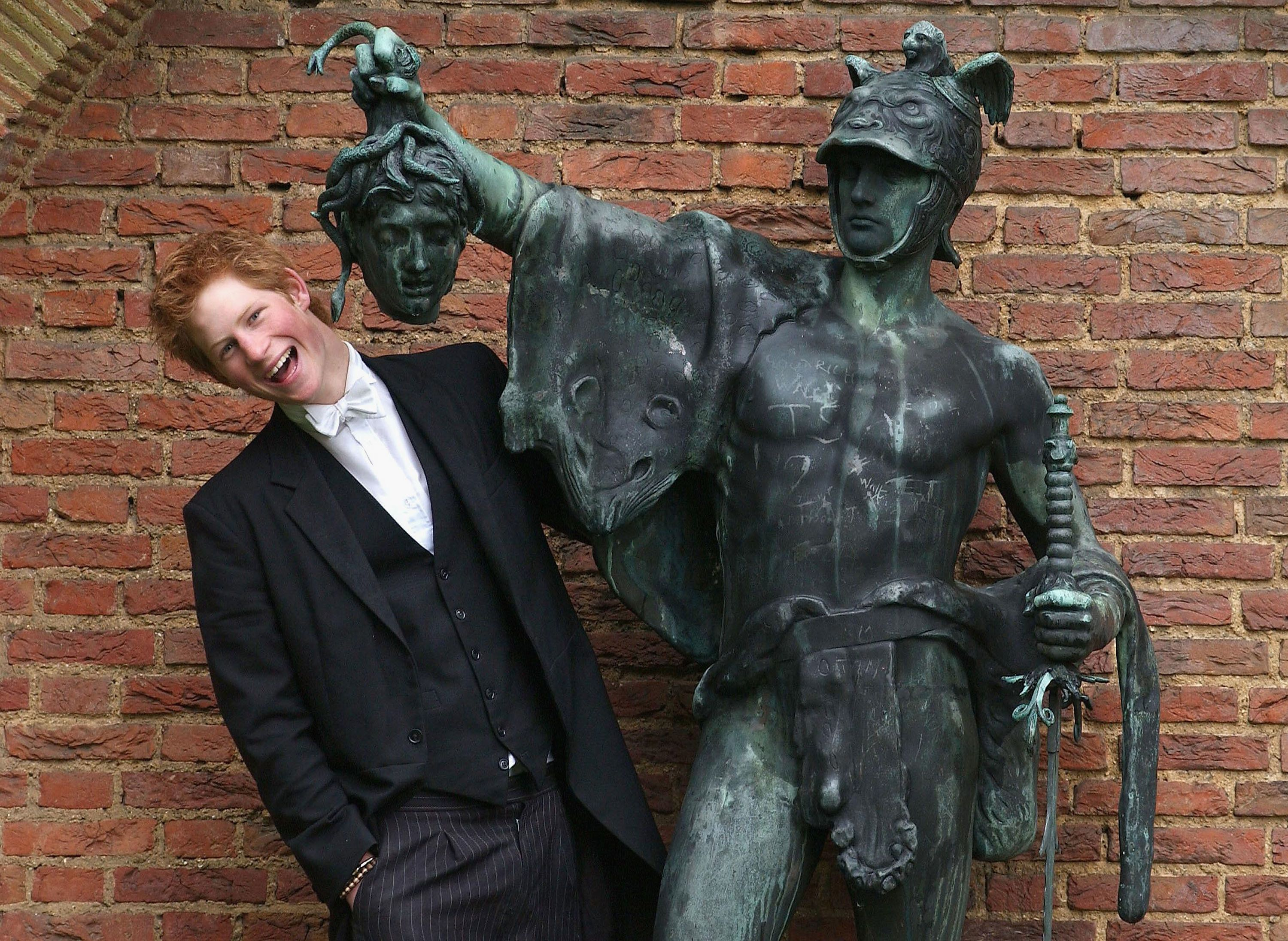 Prince Harry poses next to a bronze statue of Perseus holding the Gorgon's head on May 12, 2003, in the King of Siam's Garden