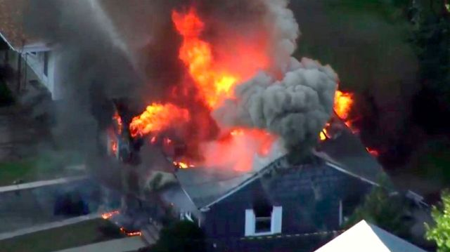 In this image take from video provided by WCVB in Boston, flames consume the roof of a home in Lawrence, Mass.