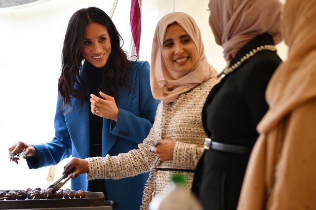 Meghan, Duchess of Sussex helps to prepare food at an event to mark the launch of a cookbook with recipes from a group of wom