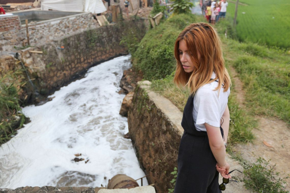 Dooley stands by the polluted Citarum River in Indonesia.