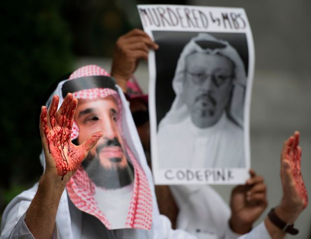 A demonstrator dressed as Saudi Crown Prince Mohammed bin Salman with blood on his hands protests outside the Saudi Embassy i