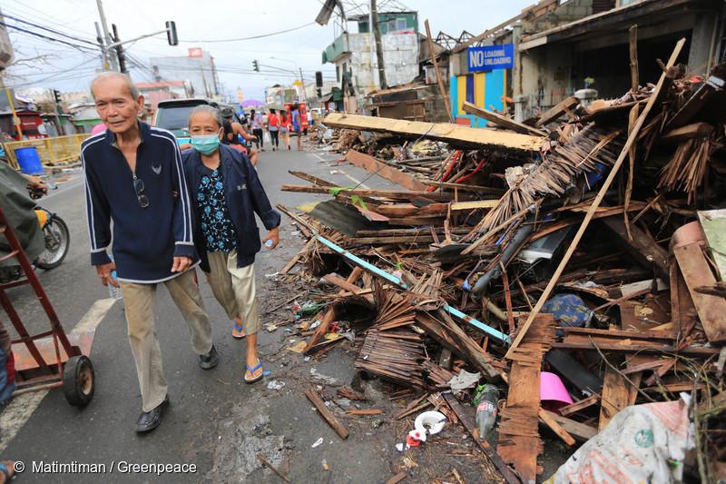 2013년 타클로반 시에서 노부부가 태풍 하이옌이 휩쓴 거리를 지나가고 있다