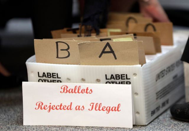 In this Oct. 30 photo, rejected mail-in ballots sit in a box as members of the canvassing board verify signatures on ballots