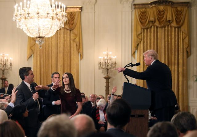 A White House intern reaches to take the microphone from CNN reporter Jim Acosta at a White House news conference Wednesday.