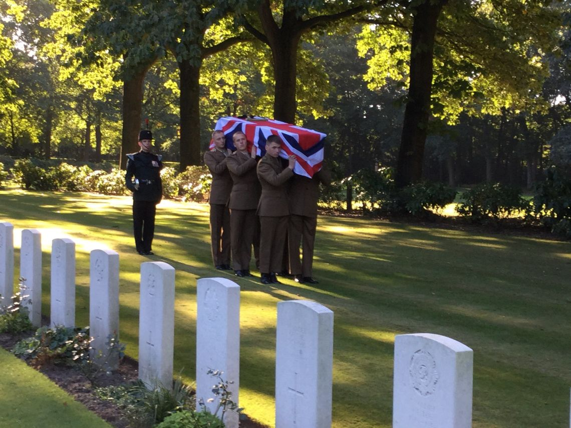 A photo of Lance Corporal Donald Noble's coffin being carried into Arnhem Oosterbeek War Cemetery by a bearer part of 5th Battalion, the Rifles