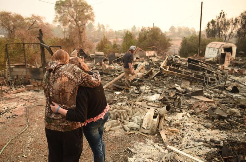 Kimberly Spainhower hugs her daughter Chloe, 13, while her husband Ryan Spainhower searches through the ashes of their burned