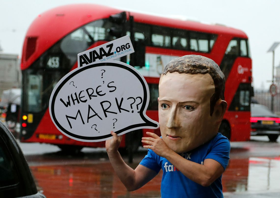 An activist wearing a Mark Zuckerburg mask stands outside the UK Parliament in Westminster.