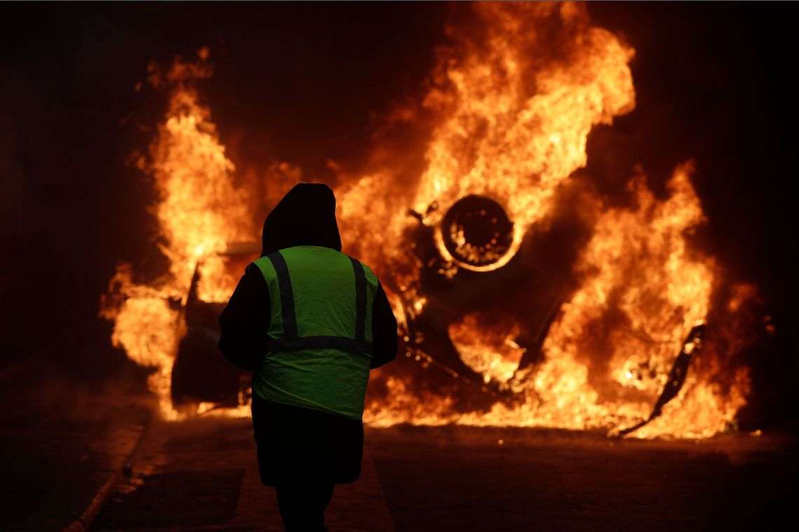 A demonstrator watches a burning car near the Champs-Elysees avenue.