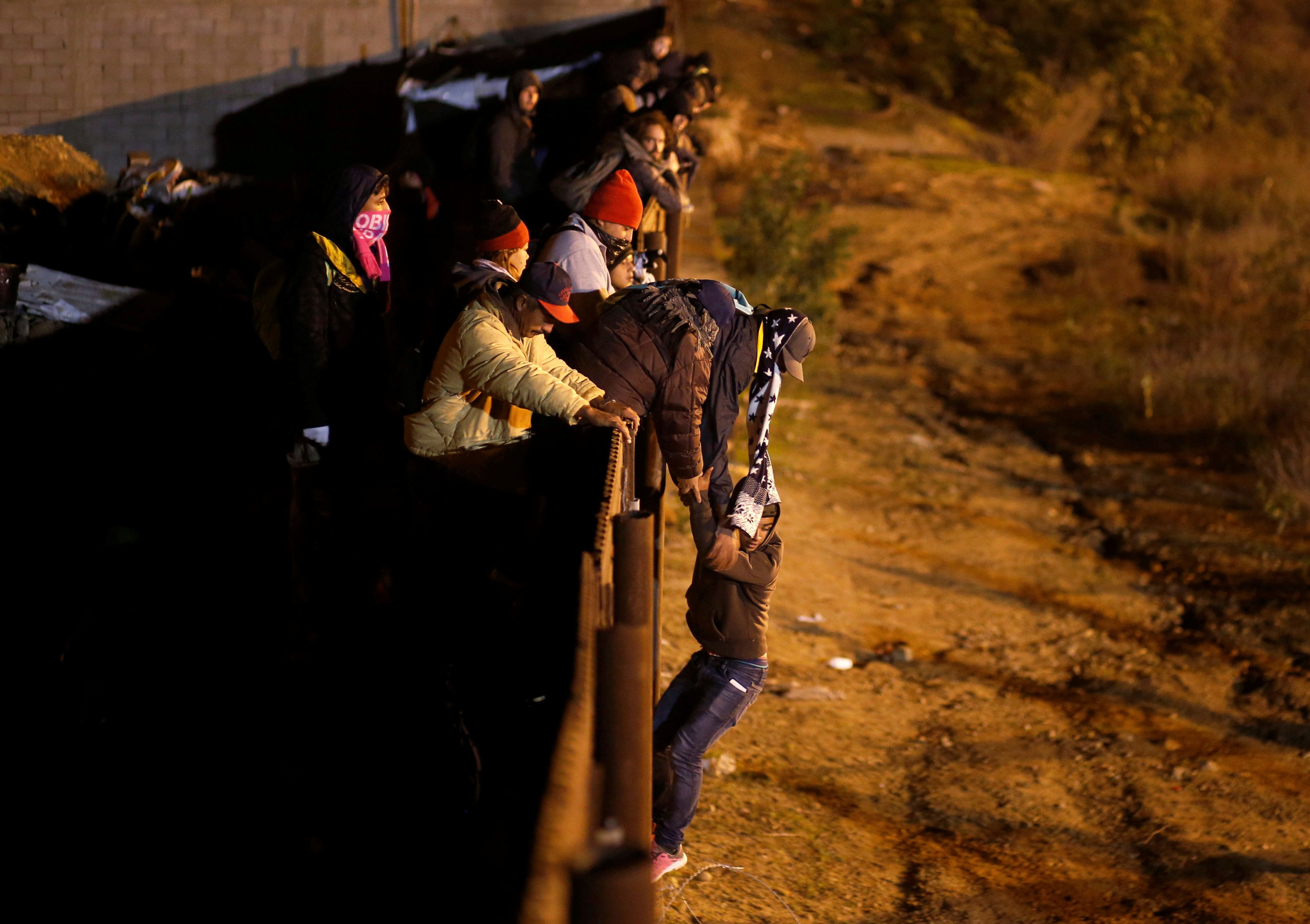 A migrant from Honduras, part of a caravan of thousands of Central Americans, jumps from the border fence to cross into the U