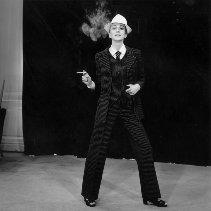 "A model strikes a masculine look wearing a pinstriped trouser suit by Yves Saint Laurent. His plainer suit for evening wear known as ""Le Smoking"" became his signature piece."