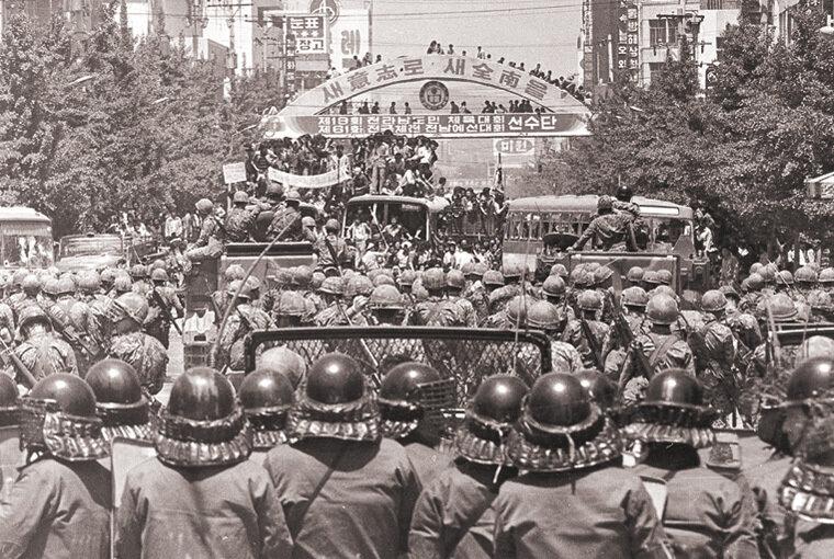 계엄령 철폐를 외치는 시민들이 광주 동구 금남로 가톨릭센터 앞에서 공수부대원 및 경찰과 대치하고 있다. 19회 전라남도민 체육대회 아치가 당시를 알려주고 있다.5.18기념재단