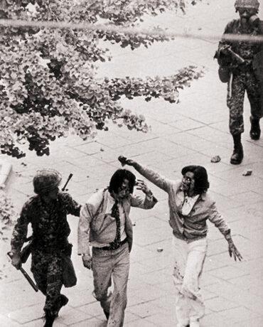 젊은 부부가 금남로2가를 지나다 공수부대가 휘두른 곤봉에 머리를 맞아 피흘린 채 끌려가고 있다.