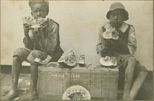 An image from 1895 depicts two black children eating wedges of watermelon.