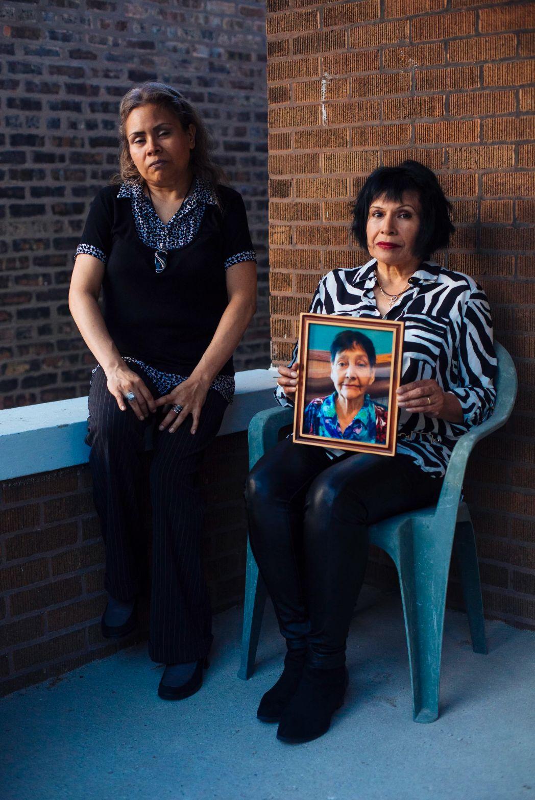 Eleanore Escamilla, left, with her sister Irma Escamilla, holding a photo of their mother, Telesfora Escamilla, who was in a