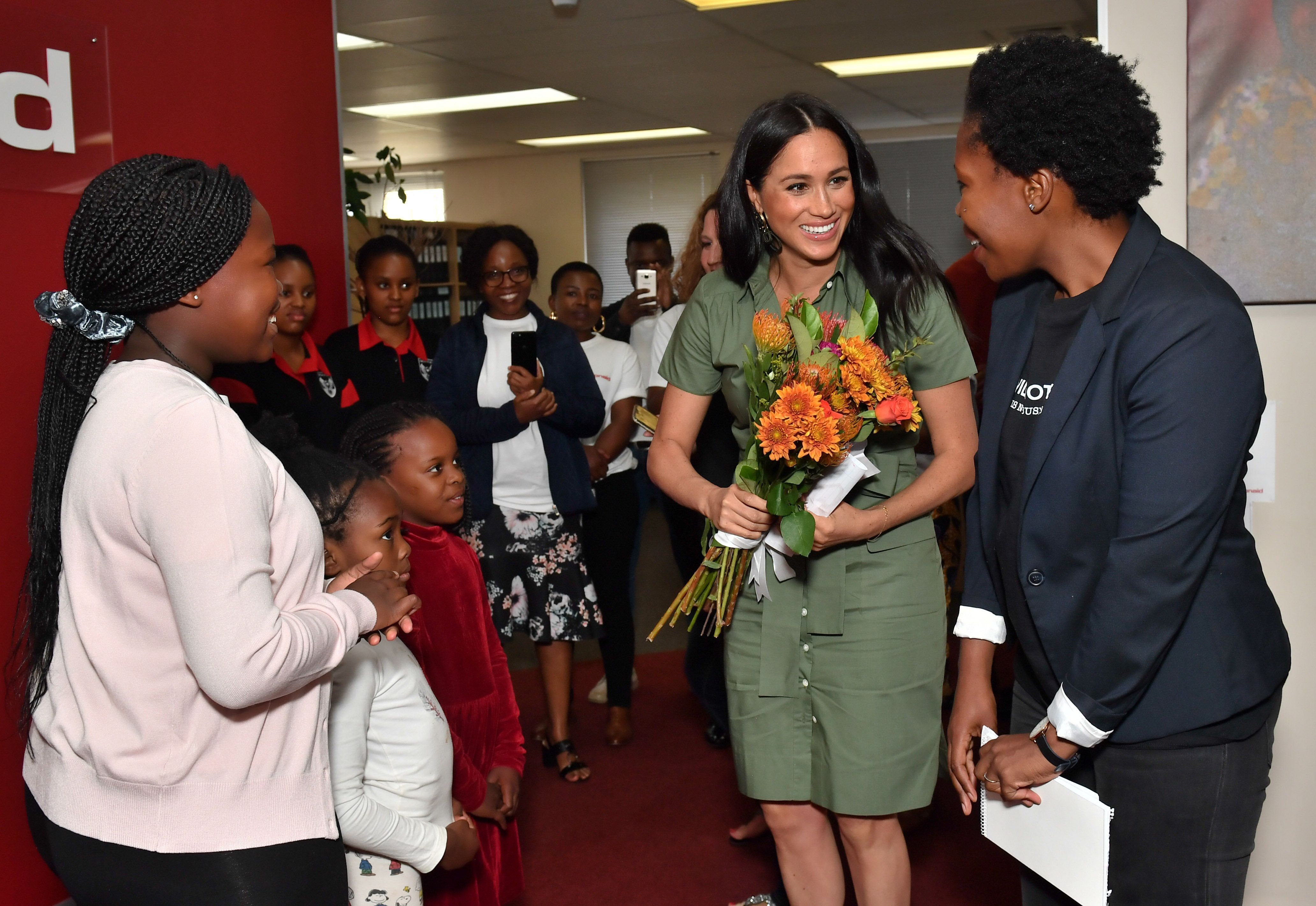 The Duchess of Sussex was presented flowers by Luyanda, age 8, during her visit to ActionAid.