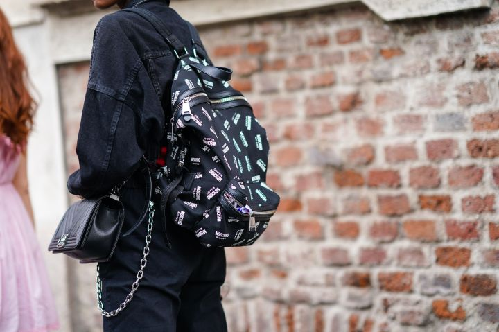 A participant in Milan fashion week wearing a Moschino backpack and a Chanel bag on September 20, 2019.