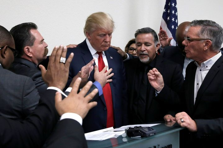 Donald Trump prays with pastors during a 2016 election campaign visit to the International Church of Las Vegas in Las Vegas,