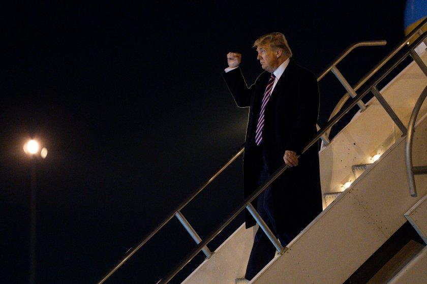President Donald Trump pumps his fist as he arrives at McCarran International Airport on Feb. 18 in Las Vegas.