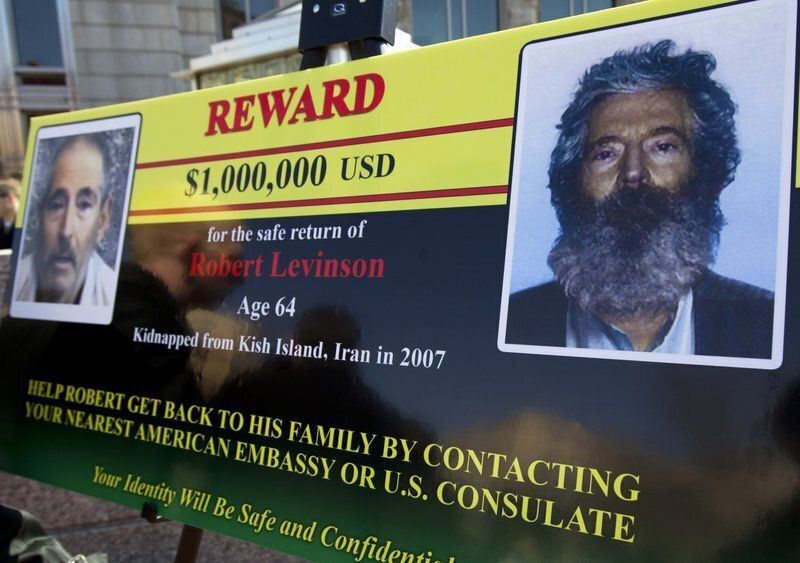 In this March 6, 2012 file photo, an FBI poster shows a composite image of former FBI agent Robert Levinson, right, and a sho