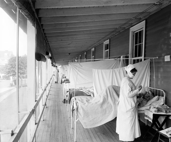 A nurse checking on a patient at the Walter Reed Hospital Flu Ward in Washington during the influenza pandemic of 1918.
