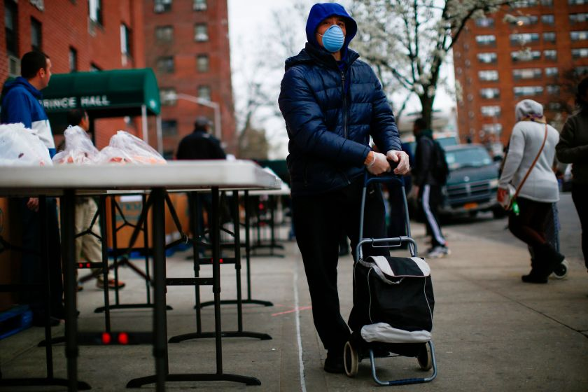 A man carries bags with food as volunteers from City Harvest distribute food in Harlem, New York City, on March 28.