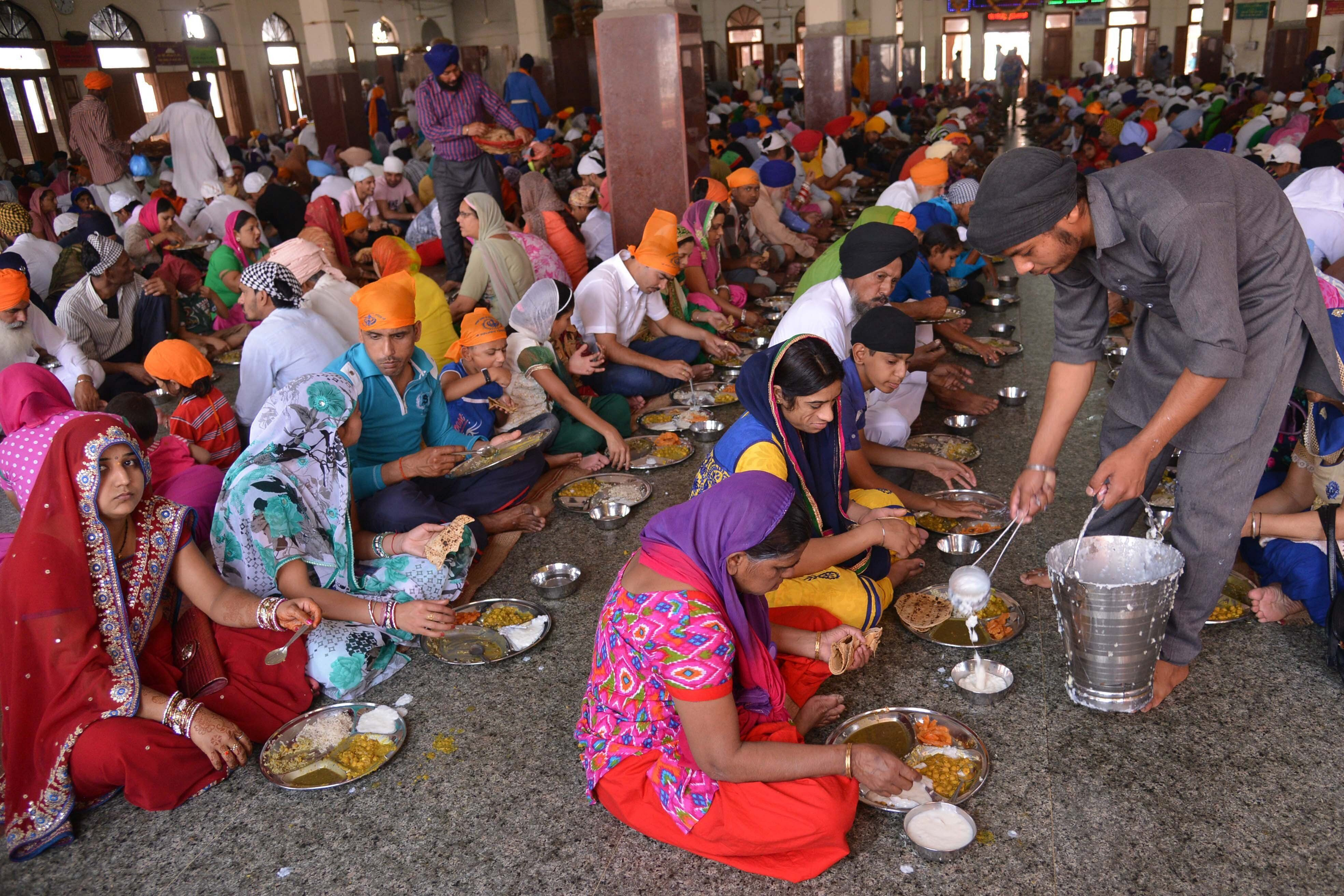 Sikh devotees eat a communal vegetarian meal, known as langar, in a hall at the Golden temple in Amritsar in 2015.