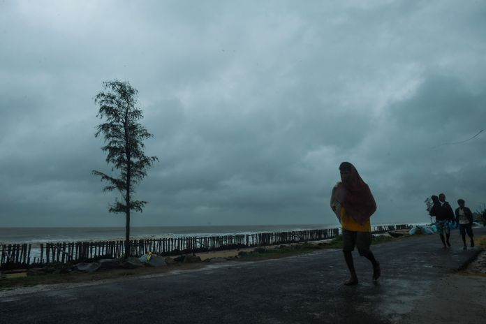 People walk along a road near the Tajpur Beach to take shelter ahead of the expected landfall of cyclone Amphan in Midnapore,