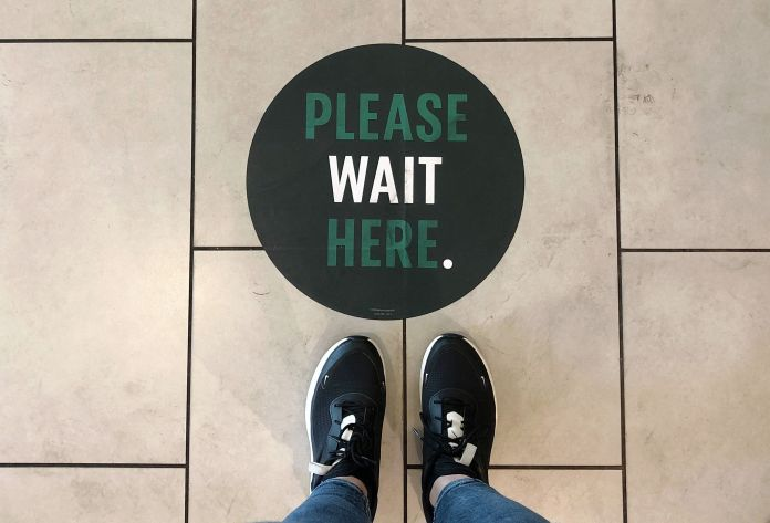 A social distancing measure sticker on the floor inside a Starbucks.