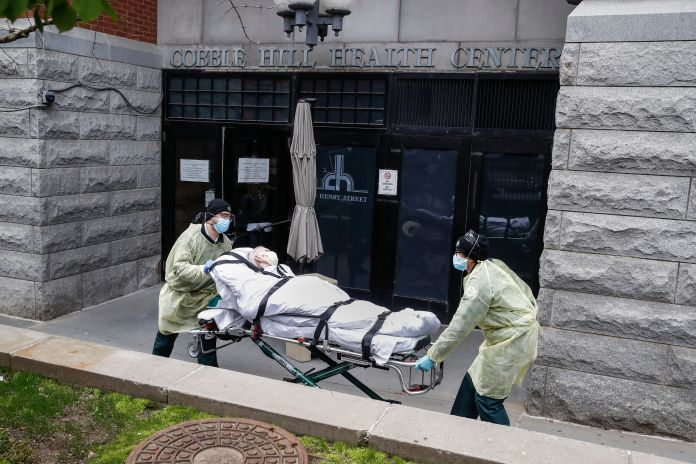FILE - In this Friday, April 17, 2020 file photo, a patient is wheeled out of the Cobble Hill Health Center by emergency medi