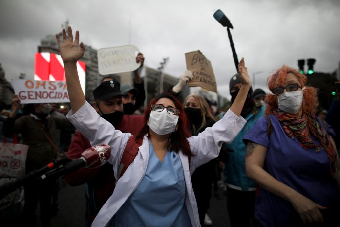 Doctors, front, demonstrate in favor of the government-ordered lockdown to help curb the spread of the new coronavirus while