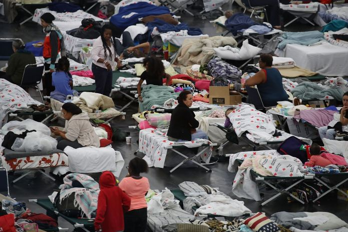 People are seen sheltering at the George R. Brown Convention Center in Houston after floodwaters from Hurricane Harvey inunda