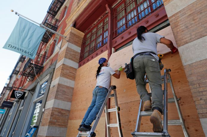 Workers board up the windows of a Tiffany's store in SoHo, New York City, on Sunday.