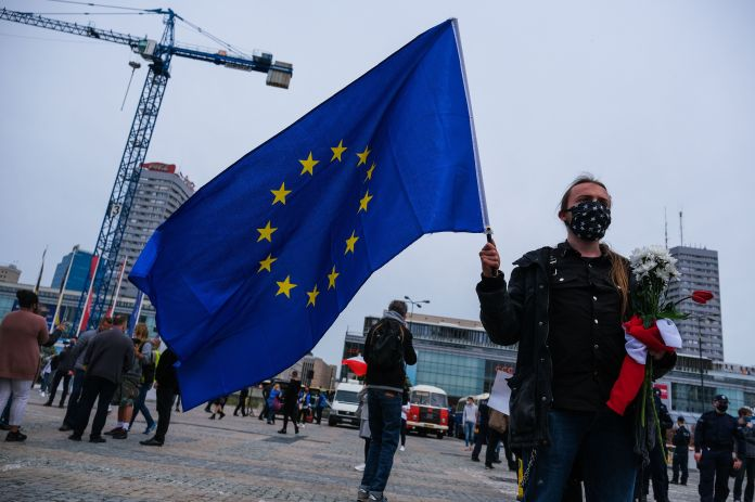 A man holding an European Union flag participates in a protest in Warsaw, Poland,on May 23, demanding more financial su