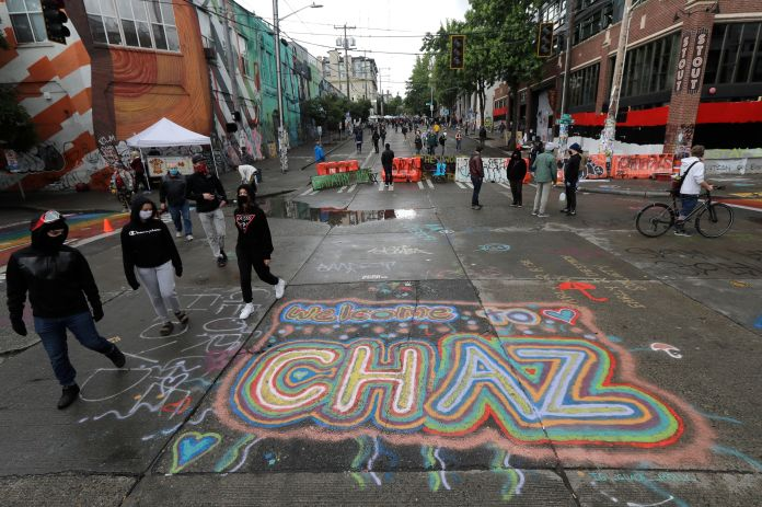"Sreet art reads ""Welcome to CHAZ"" on Thursday inside what is being called the Capitol Hill Autonomous Zone in Seattle. Follow"