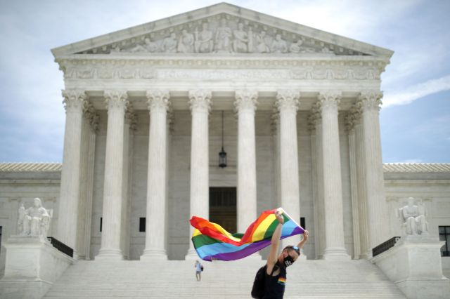 Joseph Fons, holding a Pride Flag, walks back and forth in front of the U.S. Supreme Court building after the court ruled tha