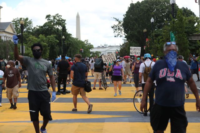 With the Washington Monument looming in the background, protesters march for racial justice on the streets of the District of