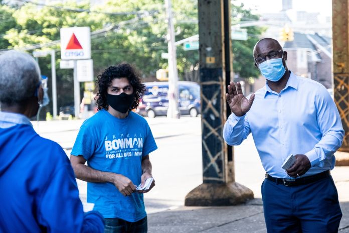 Jamaal Bowman, right, greets people outside of a subway station on Wednesday. He argues that Rep. Engel's seniority has not d