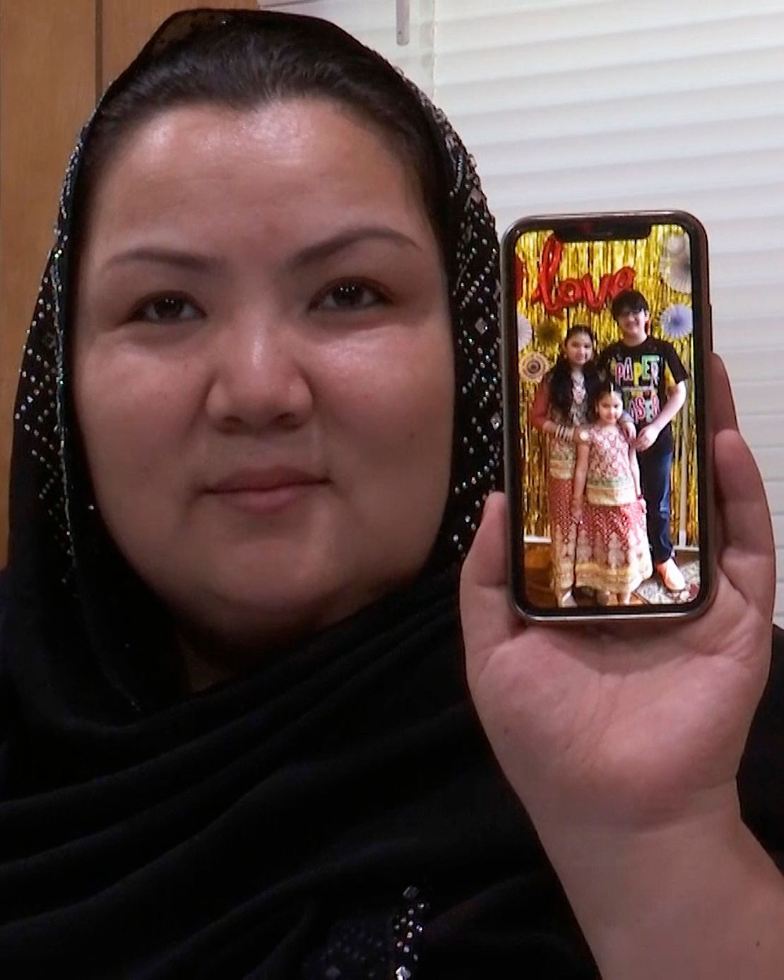 In this image from video, Zumret Dawut, a Uighur woman from China's far western Xinjiang region, holds a phone with a picture