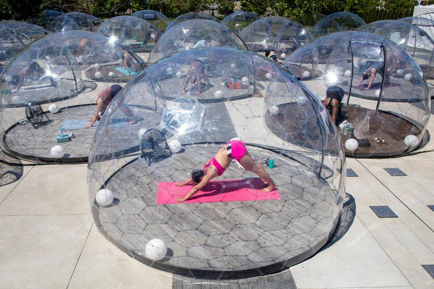 Menschen nehmen an einem Outdoor-Yoga-Kurs des LMNTS Outdoor Studio teil, in einer Kuppel, um soziale Distanzierung zu fördern ...