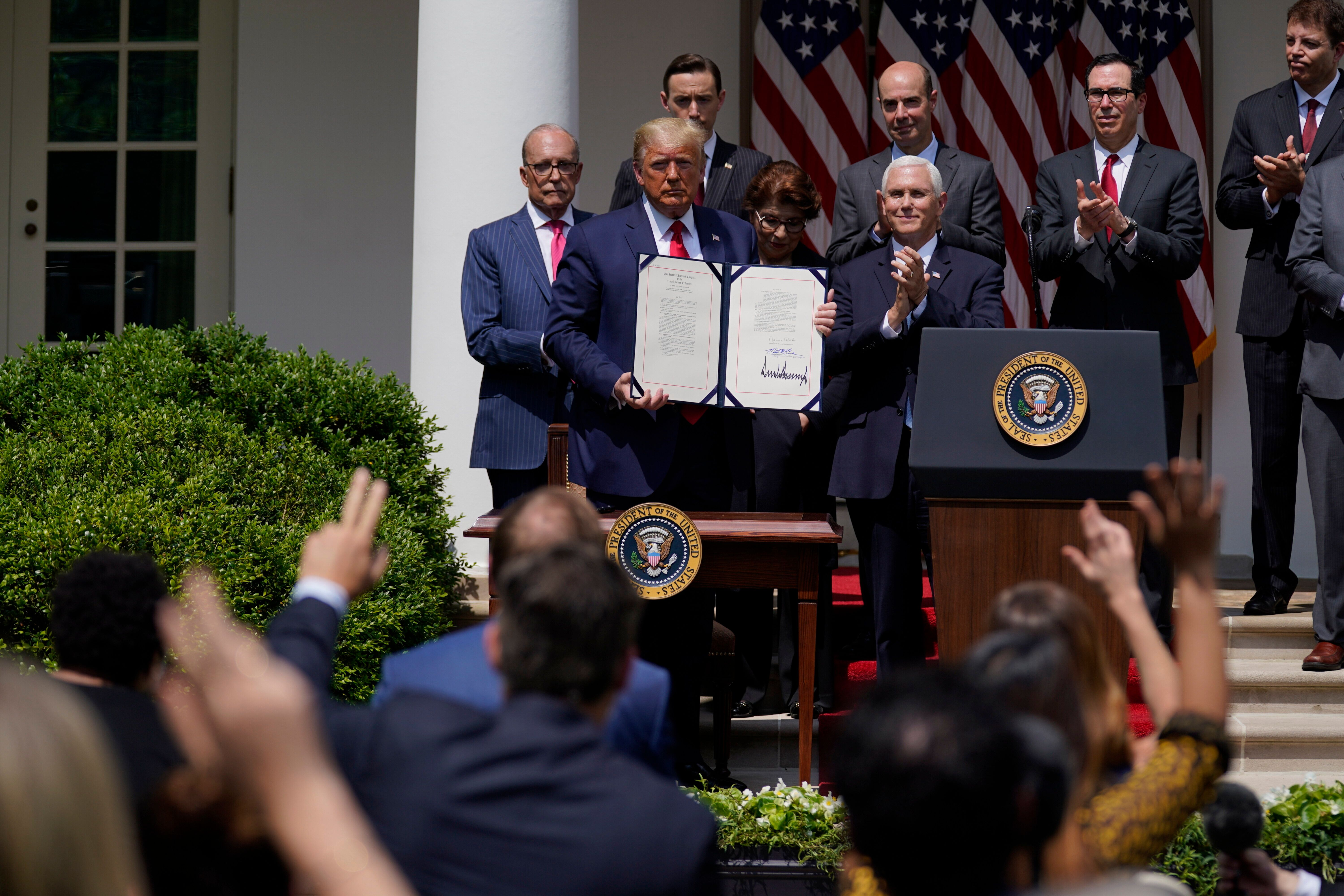President Donald Trump poses for a photo after signing the Paycheck Protection Program Flexibility Act during a news conferen