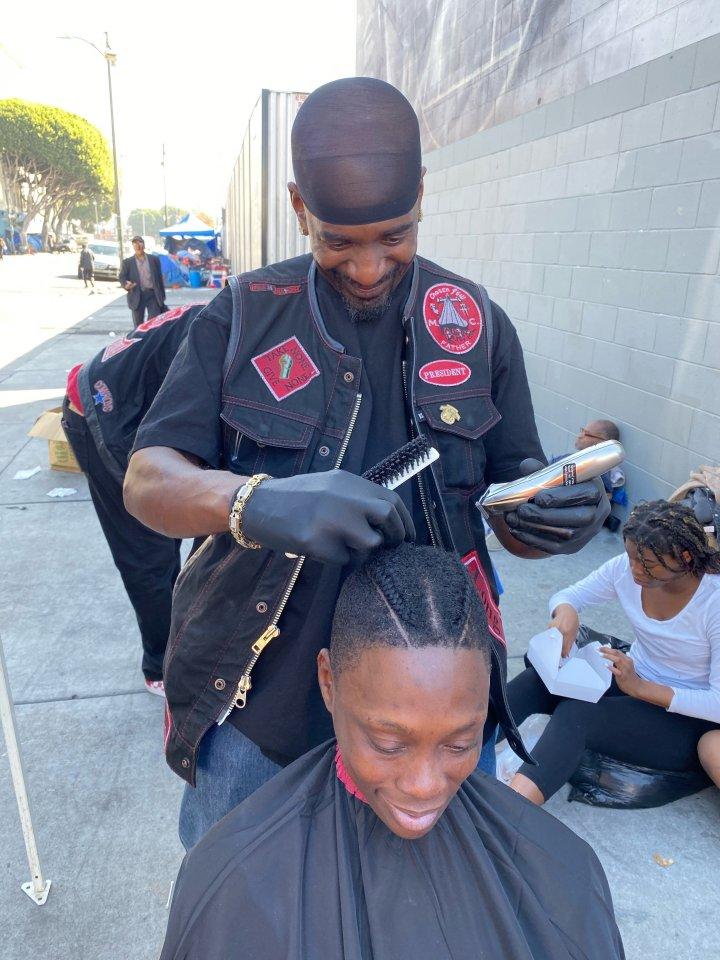 A Beauty2theStreetz volunteer braids a client's hair.