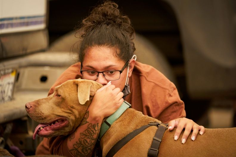 Inelva Gonzalez, of Armona, Calif. kisses her dog SayD in a marina where campers were being held due to impassable roads.&nbs