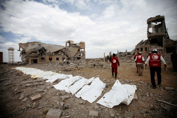 Red Crescent medics walk next to bags containing the bodies of victims of Saudi-linked airstrikes on a Houthi detention cente